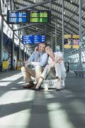 Germany, Leipzig-Halle, Airport, Businessman and businesswoman sitting on - stock photo