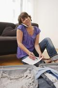 Stock Photo of Germany, Leipzig, Woman using mobile phone, suitcase in foreground