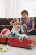 Germany, Leipzig, Mother and daughter (4-5) packing suitcase, mother using phone Stock Photos
