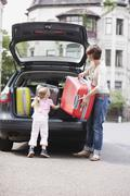 Germany, Leipzig, Mother and daugher (4-5) loading luggage into car Stock Photos