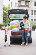 Germany, Leipzig, Mother and daugher (4-5) loading luggage into car - stock photo
