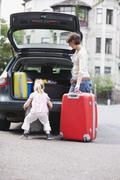 Germany, Leipzig, Mother and daughter (4-5) loading luggage into car - stock photo