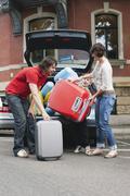 Germany, Leipzig, Family loading luggage into car - stock photo