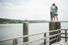 Germany, Bavaria, Ammersee, Young couple standing on wooden post - stock photo