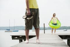Germany, Bavaria, Ammersee, Couple on jetty, woman holding floating tire Stock Photos