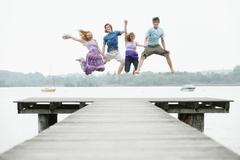 Germany, Bavaria, Ammersee, Four friends on jetty jumping in air - stock photo