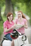 Germany, Bavaria, Young couple with map on motor scooter - stock photo