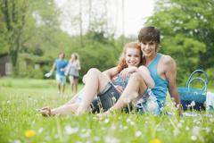 Germany, Bavaria, Young couple sitting in meadow, persons in background Stock Photos
