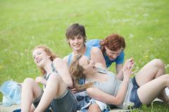Germany, Bavaria, Four friends in meadow, laughing, portrait - stock photo
