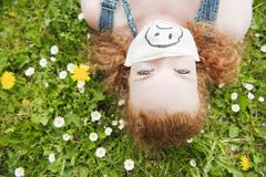 Germany, Bavaria, Young woman lying in meadow, elevated view Stock Photos