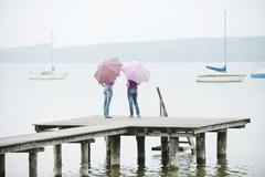 Germany, Bavaria, Ammersee, Two Women standing on jetty, holding umbrellas,  - stock photo