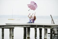 Germany, Bavaria, Ammersee, Women on jetty throwing umbrellas in air, portrait - stock photo