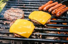 Hamburgers with cheese and hot dogs on grille Stock Photos
