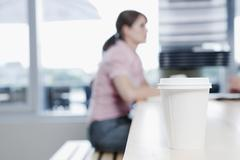 Stock Photo of Germany, Cologne, Plastic cup in foreground, woman sitting in background of cafe