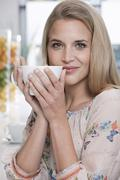 Stock Photo of Germany, Cologne, Young woman in cafe holding a cup of coffee, portrait,