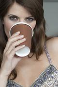 Stock Photo of Germany, Cologne, Young woman drinking cup of coffee, portrait, close-up
