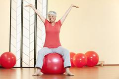 Senior woman sitting on gymnastic ball, smiling, portrait Stock Photos