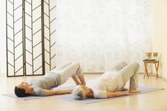 Two women arching back on gym mat - stock photo