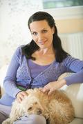 Woman sitting on a sofa with dog on her lap - stock photo