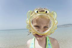 Spain, Mallorca, Girl (4-5) on the beach wearing diving goggles, portrait Stock Photos