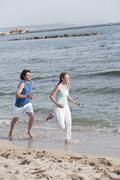 Spain, Mallorca, Couple jogging at the beach - stock photo