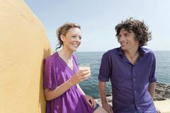 Stock Photo of Spain, Mallorca, Couple on terrace, ocean in background