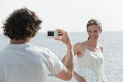 Spain, Mallorca, Man taking a photograph of a woman - stock photo