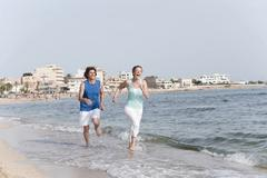 Spain, Mallorca, Couple jogging across beach Stock Photos