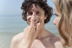 Stock Photo of Spain, Mallorca, Woman applying suncream on man's nose