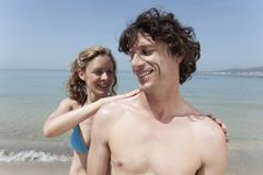 Spain, Mallorca, Woman applying suncream on man's shoulder - stock photo