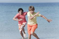Spain, Mallorca, Father and son (8-9) running across beach - stock photo
