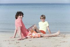 Spain, Mallorca, Father and son (8-9) sitting on beach Stock Photos