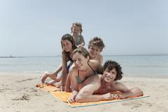 Spain, Mallorca, Family lying on beach Stock Photos
