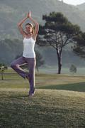 Spain, Mallorca, Woman excercising yoga, tree position - stock photo
