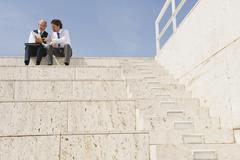 Stock Photo of Spain, Mallorca, Business men sitting on stairs holding documents