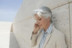 Spain, Mallorca, Senior Businesswoman using mobile phone - stock photo