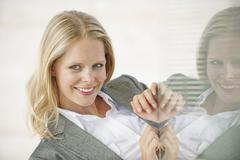 Businesswoman smiling, reflection in glass pane Stock Photos