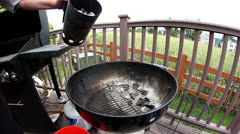 Pouring brickettes onto grill for barbequing Stock Footage