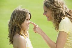Spain, Mallorca, Mother touching daughter's (10-11) nose, smiling, side view, Stock Photos