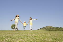 Spain, Mallorca, Mother and children (4-5), (10-11), walking across meadow Stock Photos