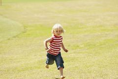 Spain, Mallorca, Boy (3-4) running across meadow - stock photo