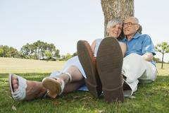 Spain, Mallorca, Senior couple sitting by tree, relaxing - stock photo
