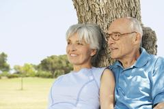 Stock Photo of Spain, Mallorca, Senior couple sitting by tree, relaxing