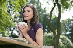 Germany, Hamburg, Woman in garden holding cup of coffee, low angle view - stock photo