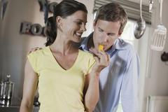 Germany, Hamburg, Couple in kitchen, man biting into piece of bell pepper Stock Photos