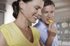 Germany, Hamburg, Couple in kitchen, man eating a piece of bell pepper, Stock Photos
