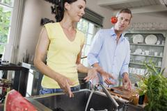 Germany, Hamburg, Couple in kitchen, fooling about with tomato - stock photo