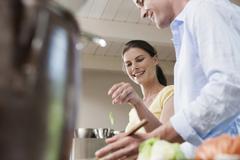 Germany, Hamburg, Couple in kitchen preparing food - stock photo