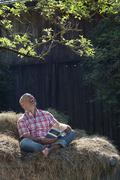 Germany, Bavaria, Senior man sitting on haystack, reading a book Stock Photos