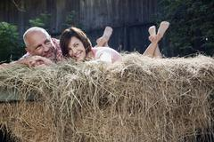 Germany, Bavaria, Couple lying on haystack - stock photo